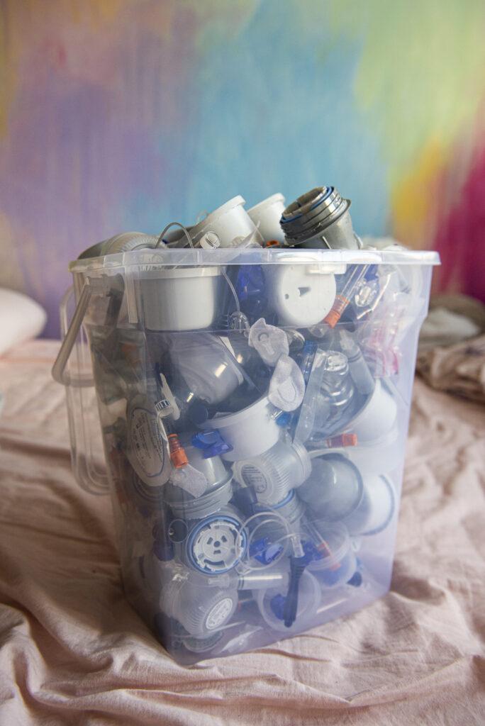 Zdjęcie przedstawia pracę artystki. Kubeł śmieci, odpadów medycznych na kontrastującym, kolorowym i wesołym tle.